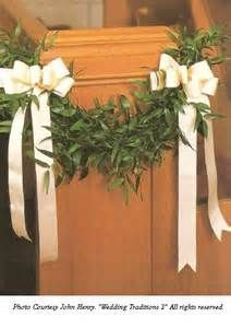 Pew bows with a greenery garland.