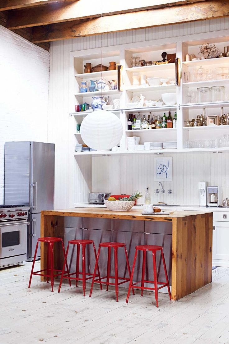 A renovated New York loft. The red stools make a bright statement against the timber island. Photography by Gaelle Boulicaut.
