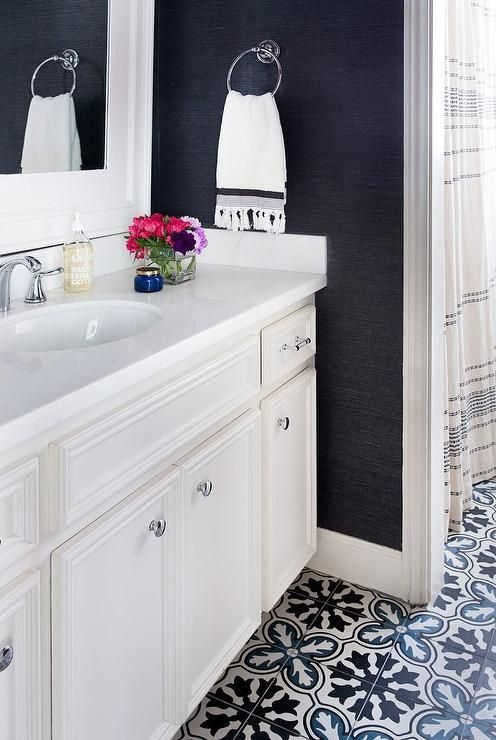 Clad in Navy Blue Sisal Wallpaper, this stunning white and blue bathroom features black and blue mosaic cement floor tiles leading to an ivory washstand accented with polished nickel knobs and a white quartz countertop fitted with an oval sink and polished nickel faucet mounted beneath a white framed vanity mirror.
