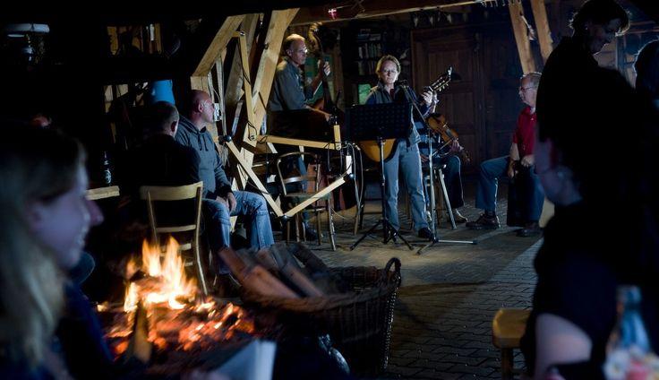 Live muziek met zang, gitaar en bas in de gemeenschappelijke ruimte met open haard vuur; gezelligheid voor de hele familie (Foto: Lars Horn)