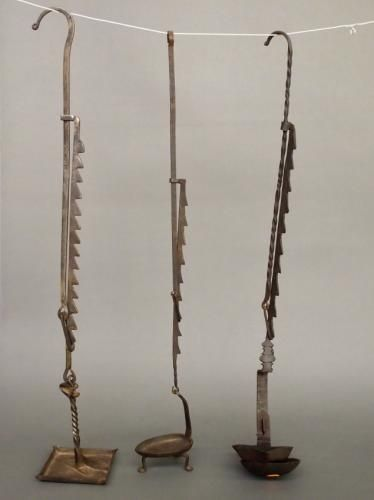 Three late 18th/early 19th century wrought iron trammells with grease lamps. Two with old surface and some oxidation, one has been cleaned. Two with painted m