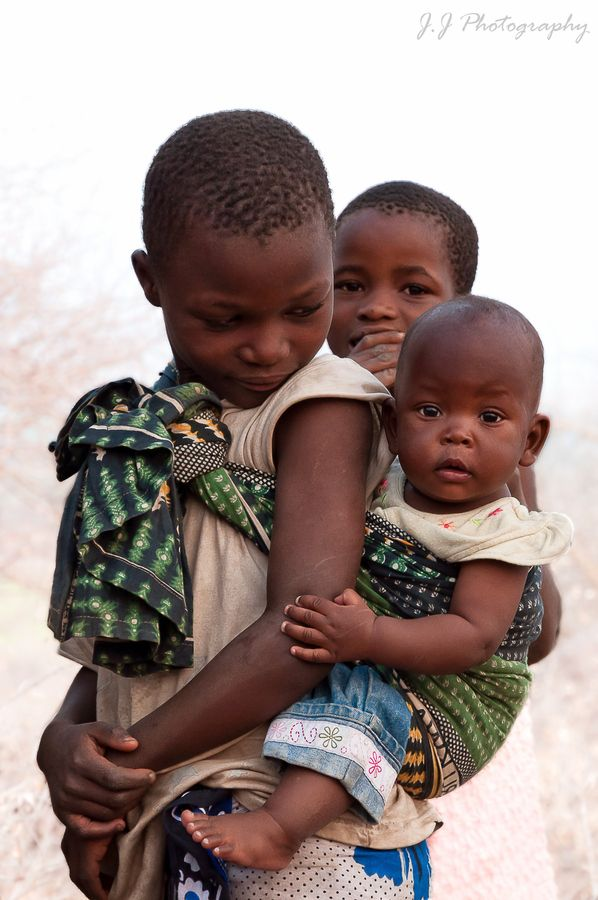 Africa | Children photographed in Tanzania | © Javier Jaso. {It is not uncommon to see young girls, carrying their younger brother or sister on their backs }