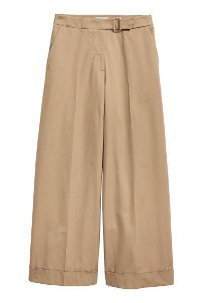Calças largas em sarja de mistura de algodão. Têm o cós alongado com fecho de metal, bolsos laterais e bolsos traseiros embutidos. Pernas retas com dobra co