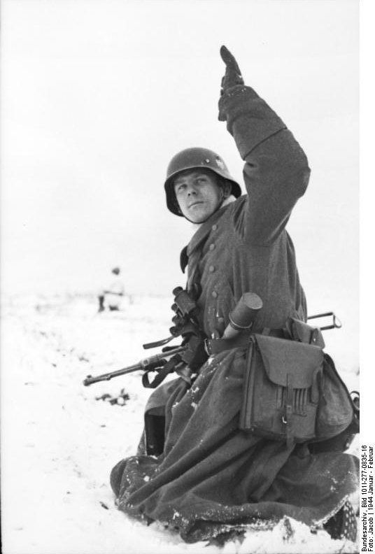German soldier in wintry terrain with MP 40 submachine gun and Model 24 Stielhandgranate (grenade tacked in belt),in Russia, Jan-Feb 1944.