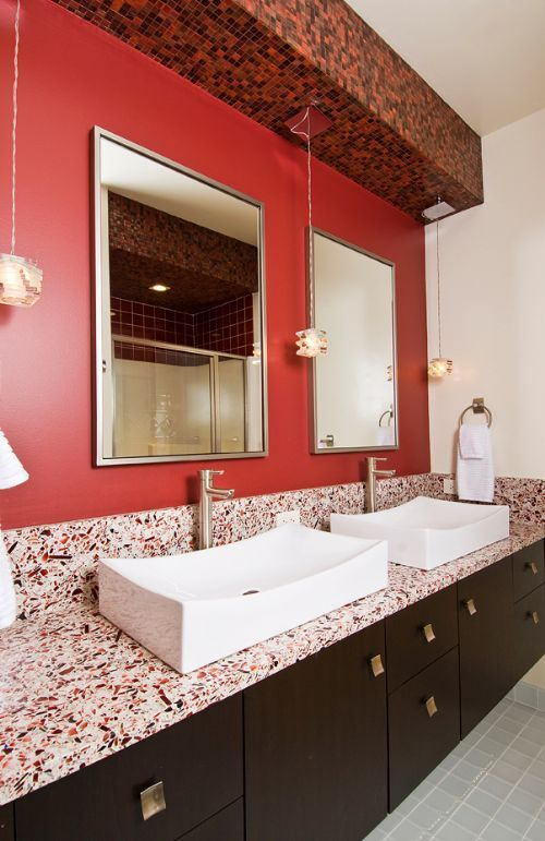 bathroom with red walls dark cabinetry and red countertops