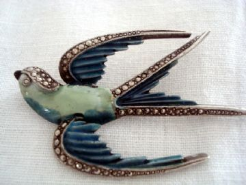 1950s brooch is in excellent order. It shows aSwallow or Swift type of bird on the wing. A romantic message is conveyed in this lovely pin. The Swallow or Swiftwhen used in antique and vintage jewellery says'Iwill return'.This vintagebrooch is finishedin two shades of blue cold enamel and has a marcasite effect decorating the head, tips of wings and forks of the tail.