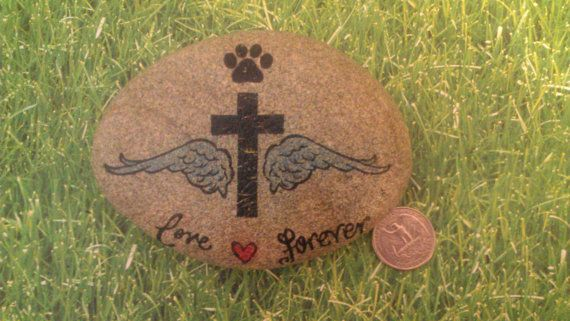 This stone has been especially painted as a memorial marker for your beloved pet. It features a black cross with sky blue wings, a paw print on top of