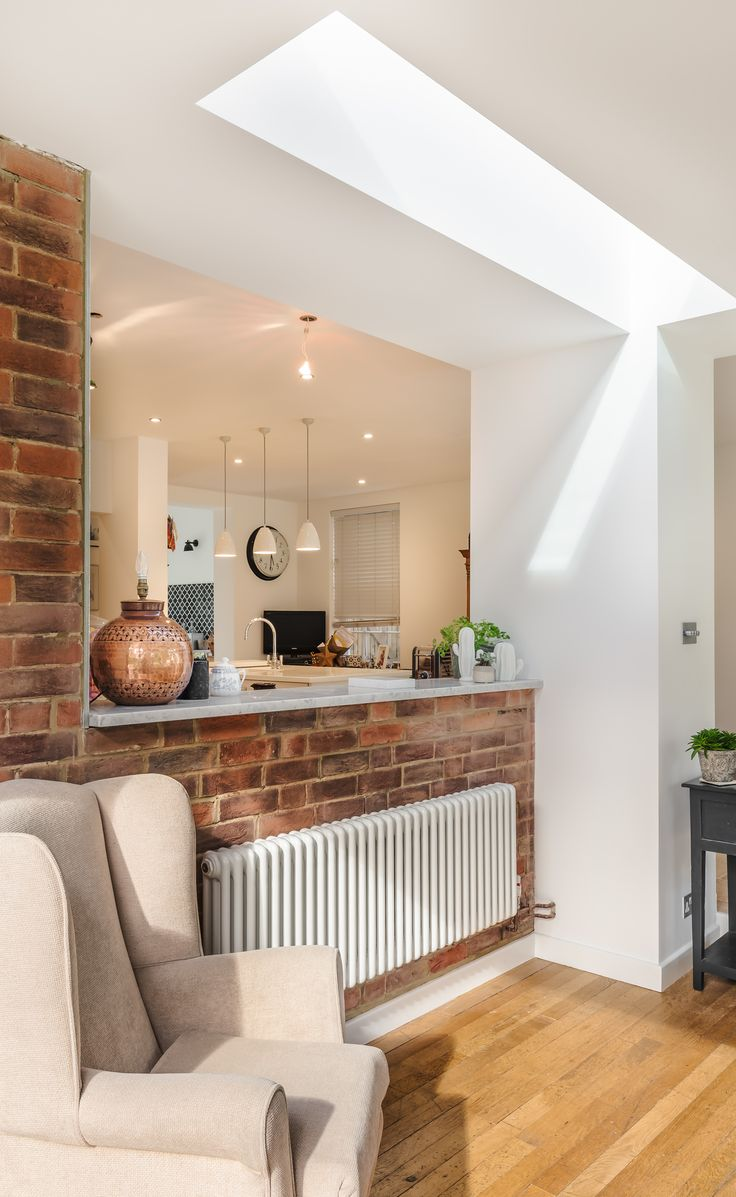It doesnt always have to be all open plan as this clevery design home in Surrey shows | feature brick wall | flat rooflight | hidden kitchen |