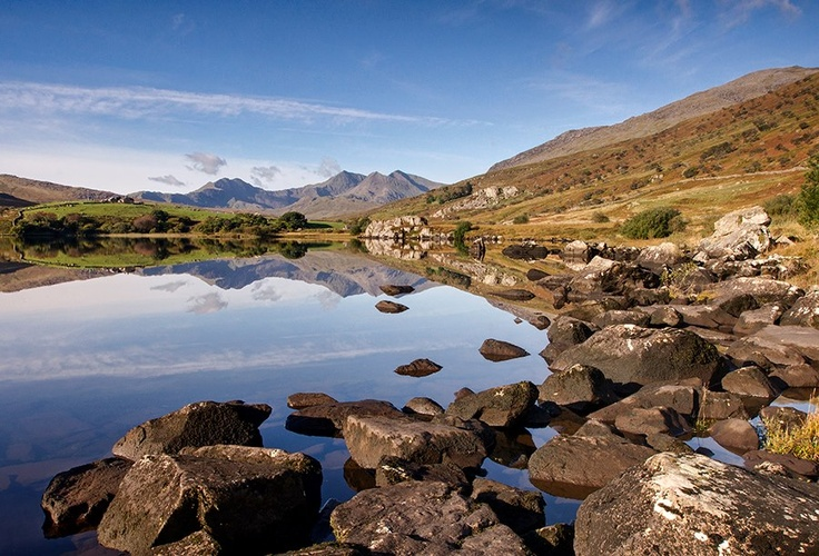 love this, must go here! Morning Over Mymbyr' - Llyn Mymbyr, Snowdonia  Take the A5 from your neck of the woods and continue through Betws-Y-Coed, til you reach Capel Curig. You can turn left just after Capel Curig (towards the Plas Brenig Outdoor Pursuits Centre), and thr lake stretches from there all the way down the road.     In the middle of the lake it goes very narrow, almost splitting it in two, theres a lay-by there and you can follow the path down :o)  kris williams photography