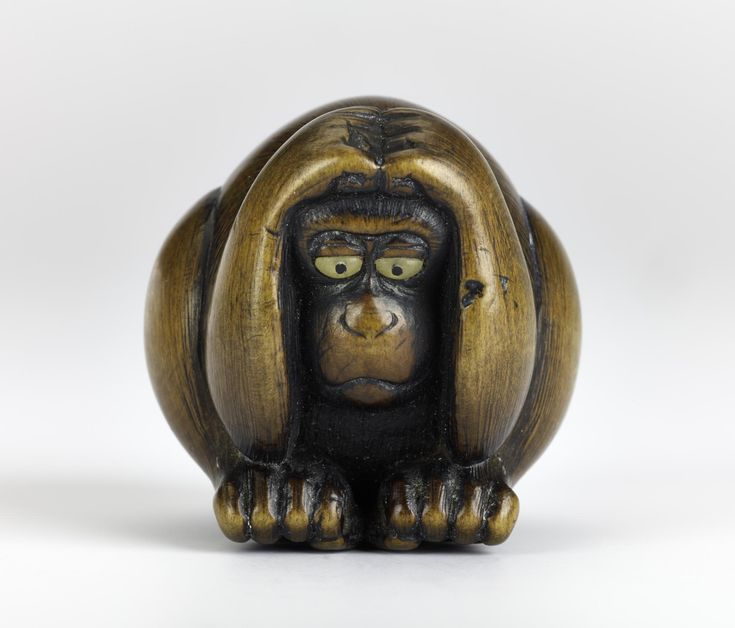 Netsuke of carved wood, a monkey crouching with hands on head, signed: Japan, by Nansui.