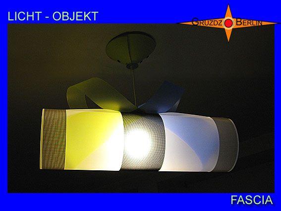Leuchte FASCIA Lampe, hier aus einem anderen Blickwinkel fotografiert, mit Baldachin, transluzent. Leuchte FASCIA Lampe mit Baldachin transluzent. Zwei farbige Bänder durchfließen bei der Pendelleuchte FASCIA den transluzenten Zylinder und geben ihm Farbe und Harmonie. Ergänzend wirken die schwarzen und weißen Streifen aus Gitternetzgewebe Batyline als Abschluss und Mitte. Faszination in Farbe und Form.