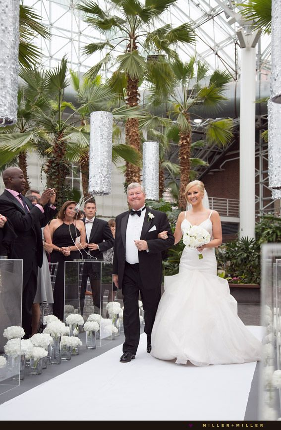 Conservatory light airy white flowers lining silver ceremony aisle