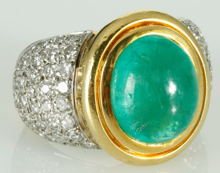 AN EMERALD AND DIAMOND DRESS RING, JENNA CLIFFORD, centred with a bezel-set cabochon-cut emerald weighing approximately 7,60cts, the shoulders highlighted by pavé-set round brilliant-cut diamonds weighing approximately 1,56cts in total, in 18ct yellow and white gold, size L, gold weight 21.4g