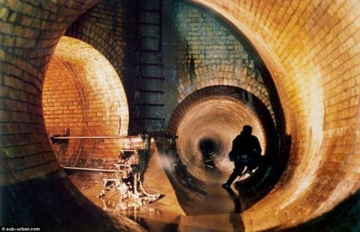 Down the tubes: A ghostly figure leans against a huge brick tunnel which was built to move sewage waters from the River Fleet into the Thame...