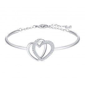 Swarovski armband 'Dear' Met het symbool van de eeuwige liefde. De armband bestaat uit een zilverkleurige bangle met schakels aan het eind, waardoor de armband makkelijk op maat is te verstellen, het sluit door een karabijnsluiting. De harten zijn verstrengeld, één van de harten is voorzien van pavé gezette Swarovski-kristallen. 5345478
