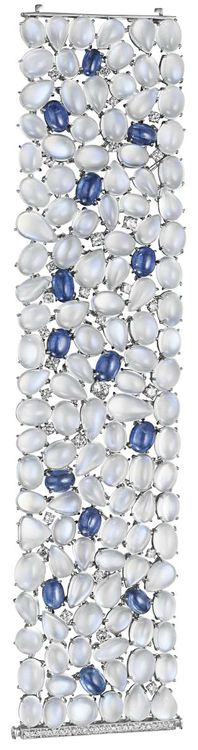 A Moonstone, Kyanite and Diamond Bracelet.     Of highly flexible design, the wide band set entirely with cabochon moonstone, accented by circular-cut diamonds and cabochon kyanites, to the pavé-set diamond clasp, mounted in 18K white gold, length 7 1/4 inches. Philips de Pury.