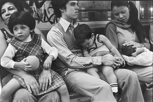 Bambini accovacciati sulle gambe dei genitori seduti su di una panchina in questa fotografia di Helen Levitt del 1965. La panchina raddoppia i posti a sedere, accoglie famiglie intere, piccoli gruppi di persone. Sulla panchina si trova sempre un posto per riposare, anche quando sembra piena. La panchina ha confidenza con tutti i corpi, ne regge il peso sollevandoli dalle pene.