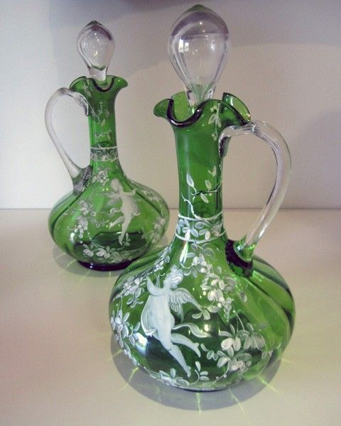 A pair of green Mary Gregory Victorian decanters, each with clear glass handle and stopper painted with figure blowing bubbles. 26 cm high