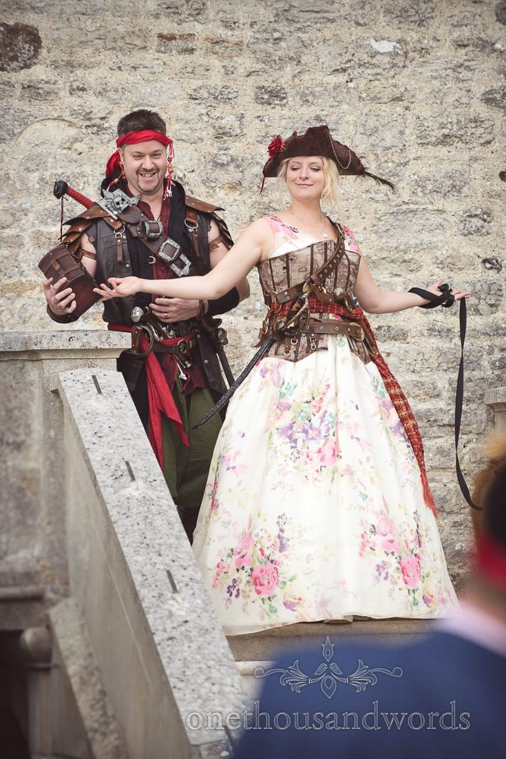 Bride and groom enter pirate themed wedding in amazing pirate fancy dress. Photography by one thousand words wedding photographers