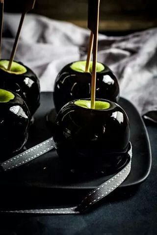 Add black gel coloring to warm carmel mix then dip apples.