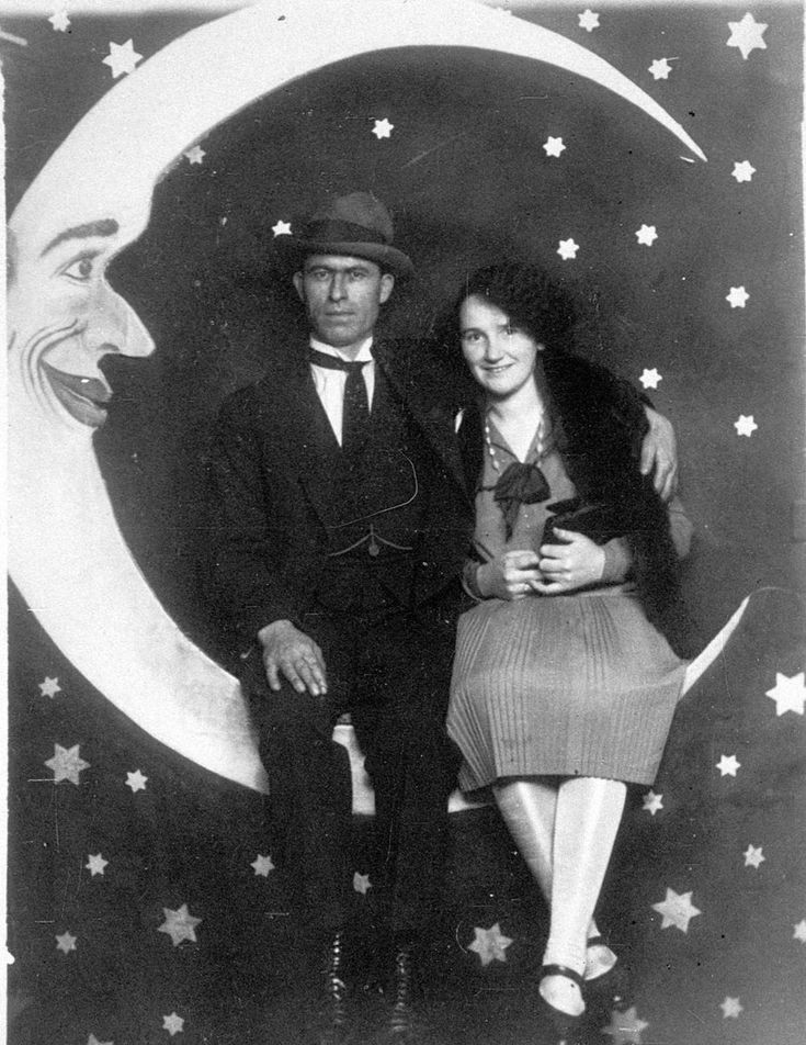Studio photograph of couple with painted backdrop of moon at Luna Park, St Kilda, Victoria/M D True. From the collection of the State Library.