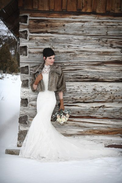 "Winter Sophisticate  This winter princess dons delicate lace, a fur stole and leather gloves to endure the frosty evening. ""This rough-hewn log cabin is the original Heber Valley milk depot from 1880,"" says Red Cliff Ranch owner Virginia Whitby.   Dress by Pronovias from The Brides' Shop, SLC, thebridesshop.net"