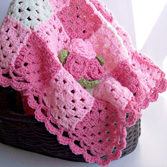 Sweet pink baby blanket is made of crochet granny squares and has a scalloped pink border. There are 3 roses appliqued on one corner. This granny