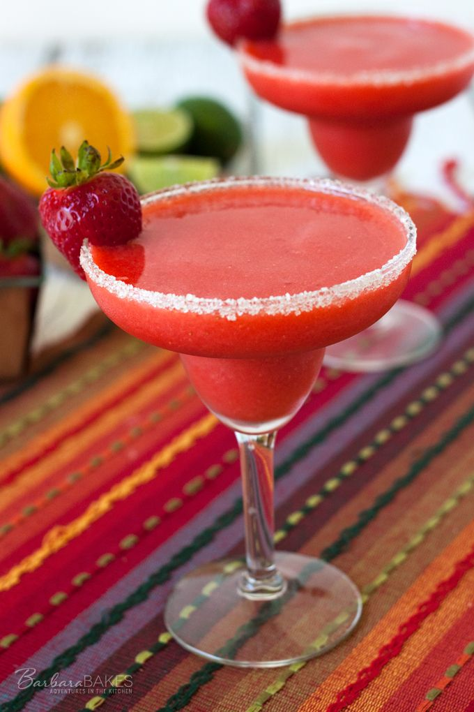 A non-alcoholic frozen sweet, tart drink made with fresh strawberries, served in a beautiful wide rim glass rimmed with coarse sugar.