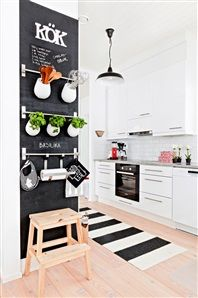 Chalkboard paint and hanging rails on that small wall at the end of the kitchen would make a nice place to store keys, pens and possibly have herbs.