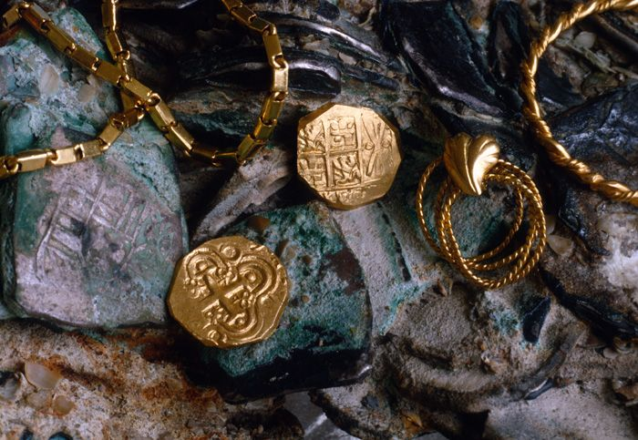 Caption 18- A pair of two escudo gold pieces from the Santa Fé de Bogotá mint, showing both the obverse and reverse of this popular 18th Century gold issue. The escudos rest on a clump of Mexico eight silver reales, whose design is clearly visible below the gold chain at the left. -1715 Fleet