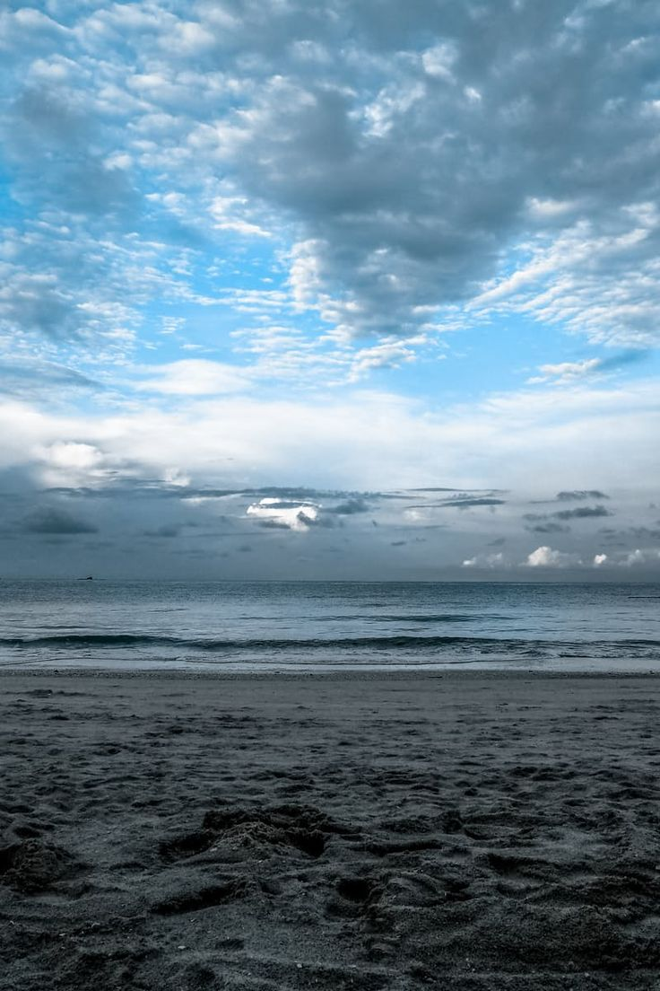 Gray Sand on Sea Shore Under Cloudy Sky during Daytime