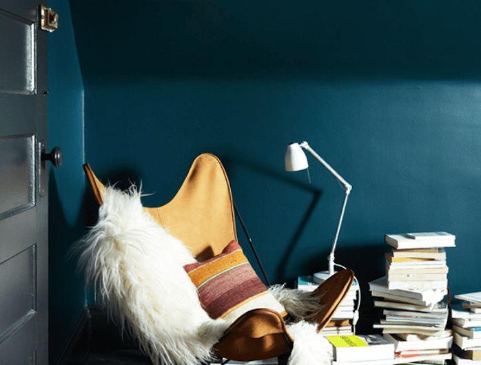 peinture bleu pétrole dans un salon sous pente, parquet noir, chaise jaune fauve, jeté de fourrure blanc, tapis oriental, piles de livres