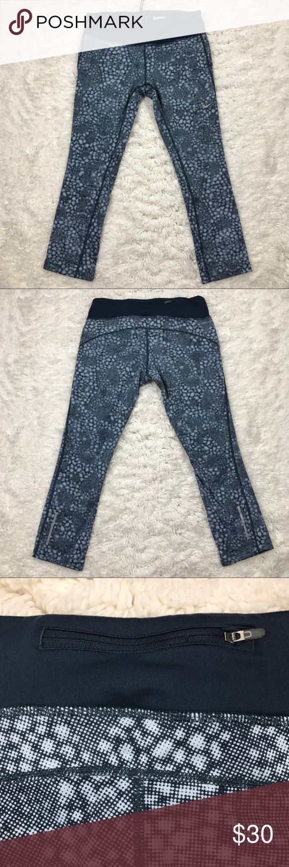 """Nike Dri-Fit Epic Run Printed Tights Nike Dri Fit Women's Epic Run Printed Tight Cropped Legging   Blue and White print with Navy Blue waist band  Size Medium  Waist 14""""  Inseam 23""""  Body 86% Polyester / 14% Spandex  Gusset lining 100% Recycled Polyester Nike Pants"""