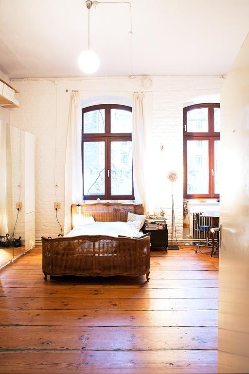 Helles, gemütliches Schlafzimmer mit dunklem Holzboden, braunem Holzbett und hohen Decken #Schlafzimmer #Berlin #WG