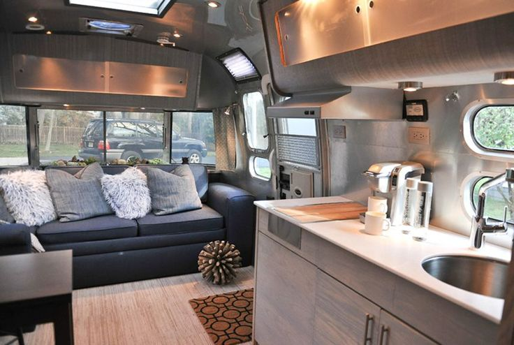 This luxe 25-foot Airstream International was decked out by Courtney Trent of Good Cottage, which rents out trailers for New York actors and directors to use on set. She removed the old sofa and installed a new one the width of a single bed and eight feet long, creating comfortable seating that can also be used for sleeping. A succulent garden is just inside the window behind the sofa, covering a bulky electronic box. See more at Courtney's Good Cottage.   - CountryLiving.com