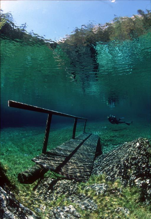 Austria's Green Lake in the Hochschwab Mountains is a hiking trail in the winter. The snow melts in early summer and creates a completely clear lake. The lake has a grassy bottom, complete with underwater trails, park benches, and bridges