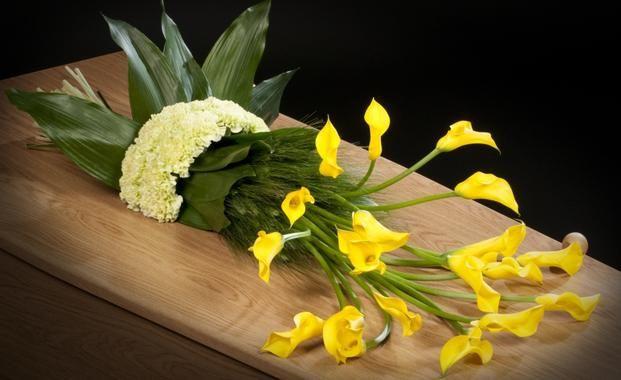 Żółte cantedeskie w wiązance nagrobnej