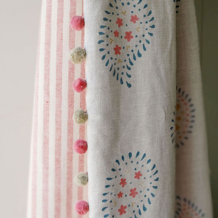 A curtain in our gorgeous Salcombe Blue Malathi Linen, backed with Rose / Ivory Stripe and finished with pom pom trim. The colours of summer for your home all year round.