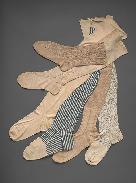 """Men's Stockings The stocking between the two blue ones would be worn with pantaloons. It is finer cotton only to a few inches above the ankle; above that, the ribbed design continues but the fiber switches to linen. The linen stocking 2nd from left may be a man's or a woman's; its knitter has simulated decorative """"clocking"""" at the ankles with a knitted openwork design."""