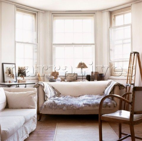 Double Glazed Bay Window Setting With Sofa And Fur Throw African Objects On Display