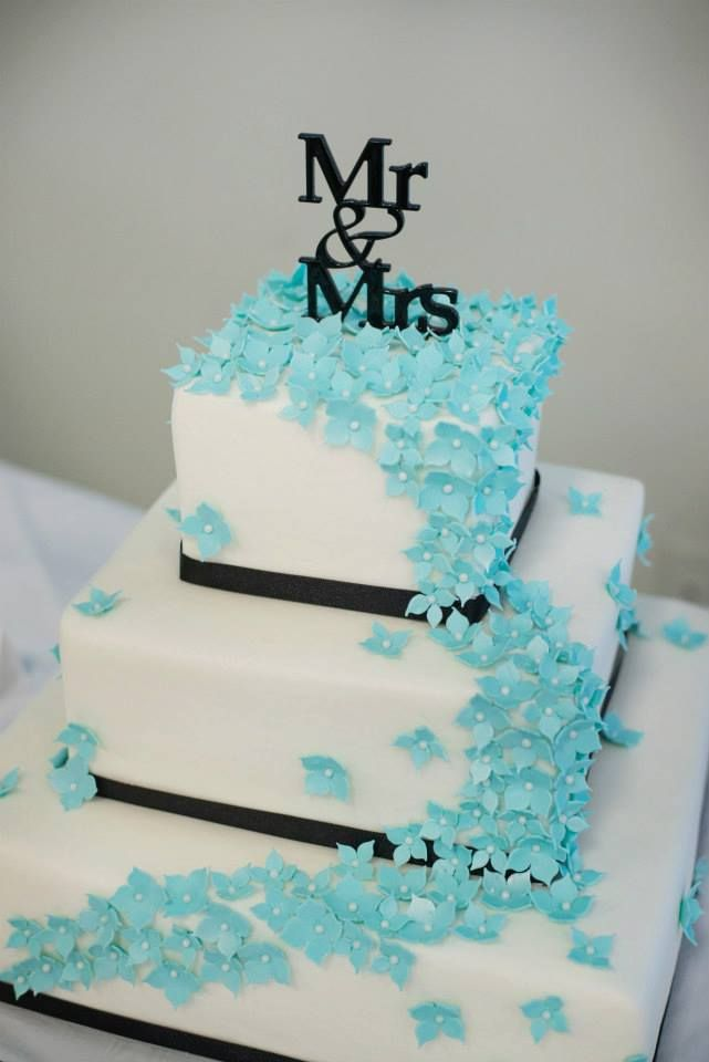 Black and white buttercream cake with cascading blue sugar flowers.  | Kansas City Wedding Cakes |