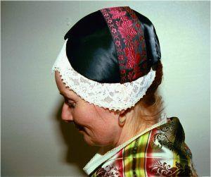 """""""Dräkt från Offerdal, Jämtland. Huvudbonad: svart bindmössa med stycke för gift kvinna. Ogift kvinna har lila bindmössa."""" Black cap for married woman, purple for unmarried."""