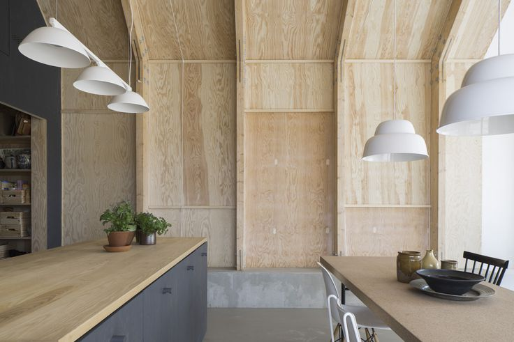Forstberg Ling House for Mother, a soaring Scandinavian kitchen in natural and stained plywood with a concrete floor that rises to form a low bench
