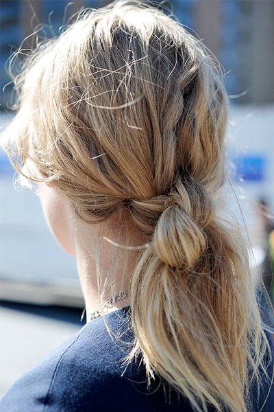 Double Knot  [1. Liberally mist the hair with Bumble & Bumble Surf Spray. 2. Scrunch the hair to create the waves. 3. Take a section of hair and sweep it across the face to create a deep side part. 4. Pull the rest of the hair and make a double knot. (Hint: just like tying your shoes!)]