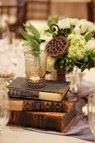 We are planning on incorporating vintage books/cigar boxes/travel memorabilia into our centerpieces- something simple like this works for me, and keeps the vaguely masculine look that we are going for