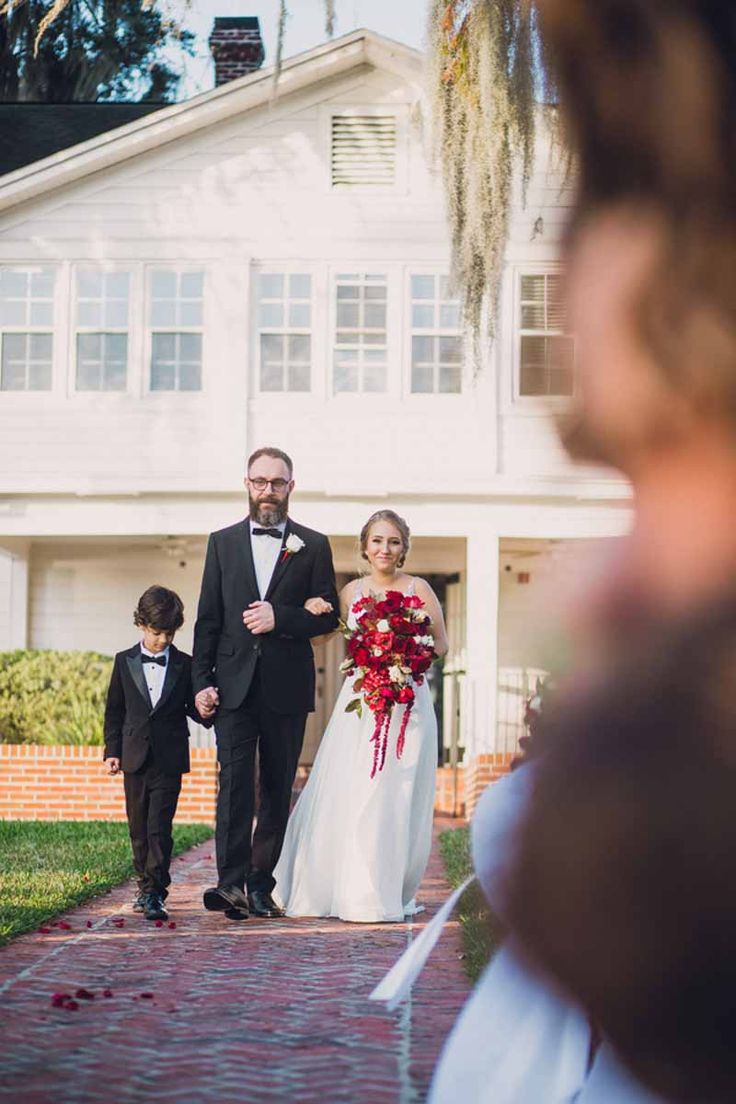 father walking bride up the aisle holding red cascading bouquet by Lee Forrest Design-Red and white Cypress Grove Estate House Wedding in Orlando, FL - Photo: Lora Rodgers Photography-Orange Blossom Bride