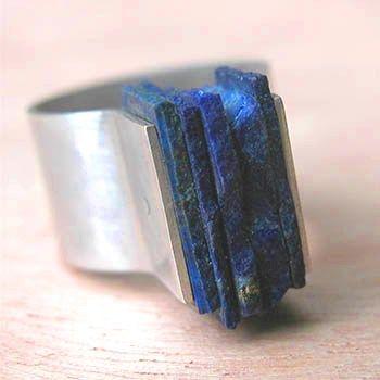 Ik heb deze ring uitgekozen omdat ik de manier van de steen plaatsen heel interessant vind. Normaal gesproken zet je een steen in een kastje. Hier zitten meerdere laagjes Lapis (edelsteen) tussen twee platen zilver gedrukt. Het geeft de ring kracht, volume en een robuust uiterlijk. Prachtig! Armande Potel-Martin.