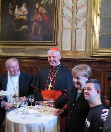 Rührende Szene am Rand der Papst-Audienz: Gianluca Quintaié (22) hatte die Aufgabe, der Kanzlerin ein Glas Wasser und ein Glas Wein zu bringen. Er fasst sich ein Herz, spricht die Kanzlerin mit Hilfe eines Kollegen an, bittet um ein Erinnerungsfoto http://www.bild.de/politik/inland/angela-merkel/kanzlerin-herzt-jungen-italiener-39873752.bild.html