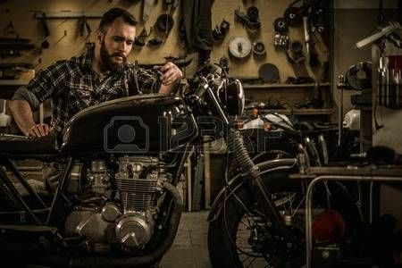 history of motorcycles: Mechanic building vintage style cafe-racer motorcycle  in custom garage Stock Photo