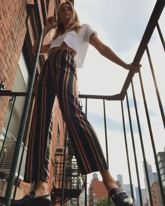 Striped fitted and flared trousers with white cropped t-shirt and trainers casual outfit style Sumer Spring